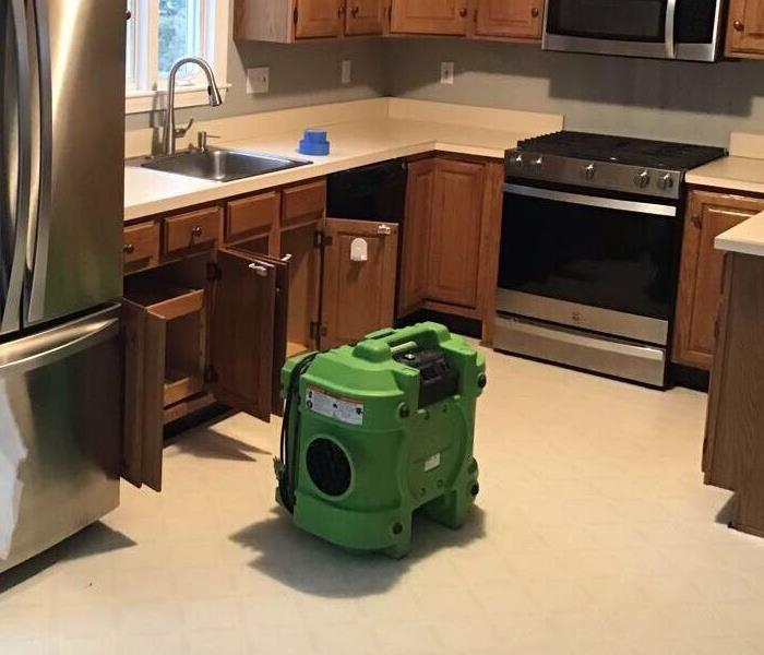 A kitchen with cabinet doors open and SERVPRO equipment on the floor.